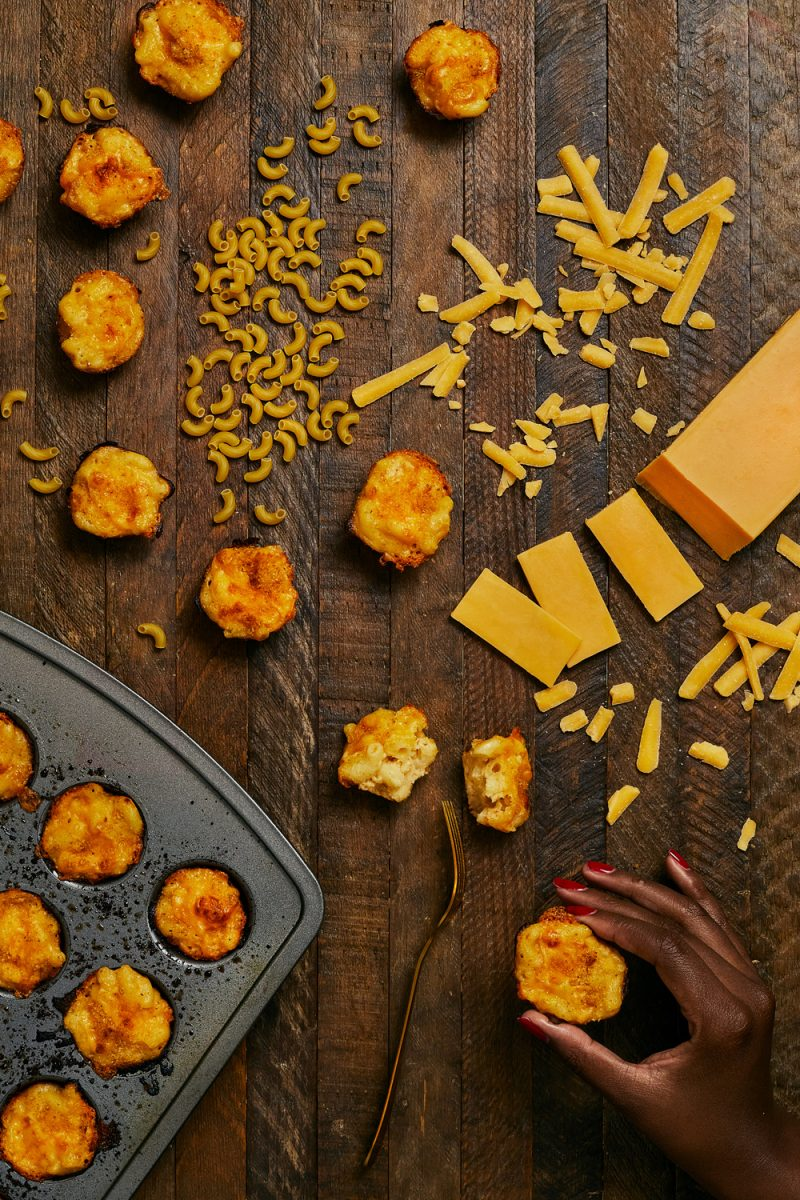 Mac and Cheese Bites by popular D.C. food blog, Alicia Tenise: image of a mini muffin tin filled with mac and cheese bites and individual mac and cheese bites next to uncooked macaroni pasta, shredded cheese, and a block of cheddar cheese.
