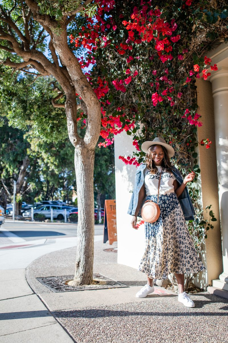 Silk Skirt by popular D.C. fashion blogger, Alicia Tenise: image of Alicia Tenise standing next to a bush with pink flowers and wearing a pleated floral sillk skirt with a felt fedora hat, white sneakers, graphic t-shirt, denim jacket, and circle bag.