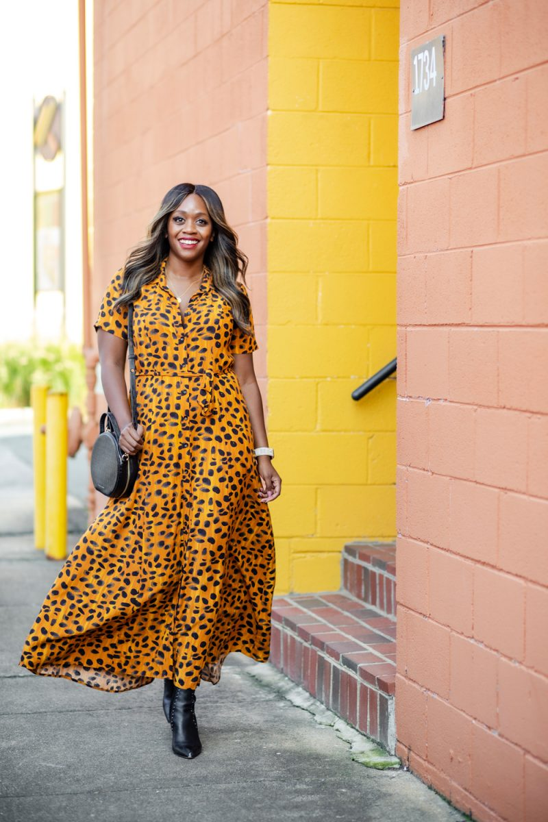 Anthropologie Vianne Maxi Shirtdress | Leopard Print Shirt Dress by popular D.C. fashion blogger, Alicia Tenise: image of Alicia Tenise walking outside next to a peach colored building and wearing a Anthropologie leopard print shirt dress, black point toe ankle boots and carrying a black circle purse.