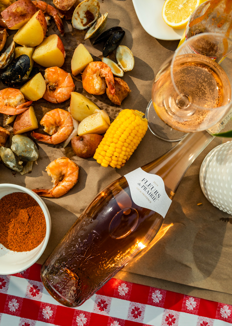 Rosé and Food Pairing Ideas   Food Pairings by popular D.C. food and wine blogger, Alicia Tenise: image of a couple glasses and bottle of rose next to a seafood broil with a gloss of rose.