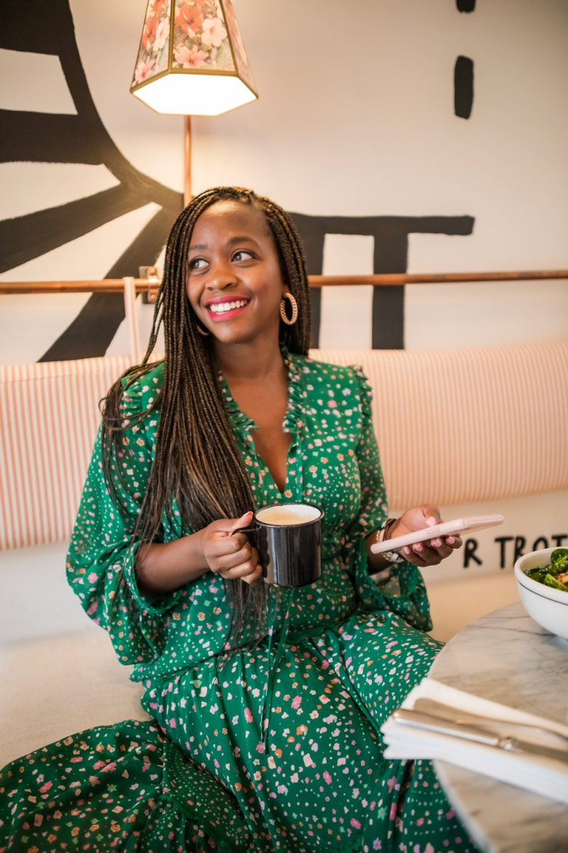 How to Customize Widgets on iPhone by popular D.C. lifestyle blogger, Alicia Tenise: image of Alicia Tenise wearing a green floral print maxi dress while sitting in a coffee shop and holding a mug of coffee and her iPhone.