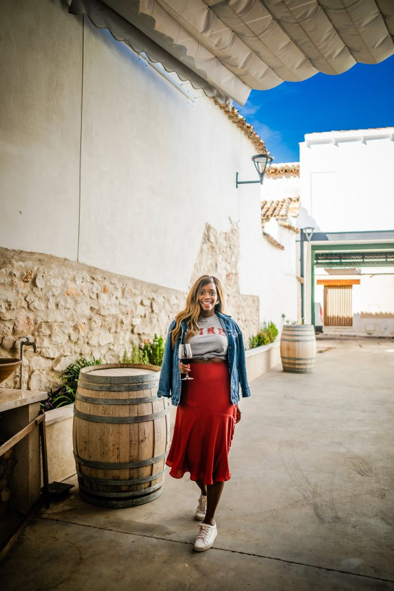 How to Style a Silk Skirt | Silk Skirt by popular D.C. fashion blogger, Alicia Tenise: image of Alicia Tenise walking down a alley way and wearing a red silk skirt, white sneakers, grey t-shirt, and denim jacket while she holds a glass of red wine.