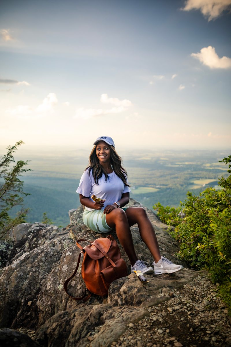 Blue Ridge Parkway Afton VA | Things to do in Charlottesville by popular D.C. travel blog, Alicia Tenise: image of Alicia Tenise sitting on a rock at the top of a mountain.