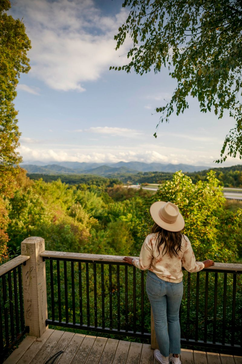 Things to do in Asheville NC by popular D.C. travel blogger, Alicia Tenise: image of Alicia Tenise standing on a balcony and looking out at the mountains.