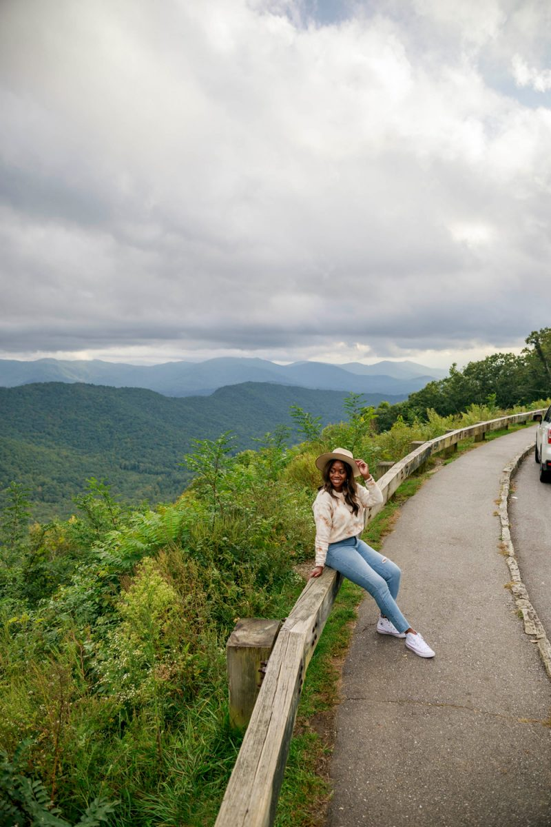 Blue Ridge Parkway Asheville | Things to do in Asheville NC by popular D.C. travel blogger, Alicia Tenise: image of Alicia Tenise sitting outside on a guardrail.