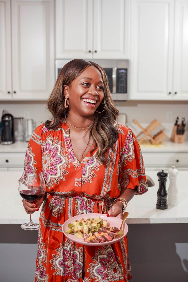 Blue Apron Review by popular D.C. food blogger, Alicia Tenise: image of Alicia Tenise standing in her kitchen and holding a plate of food made from Blue Apron supplies.