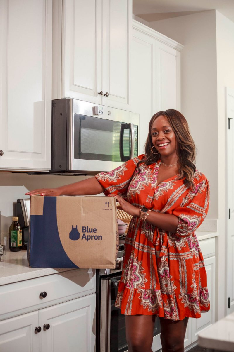 Blue Apron Review, Anthropologi Isabel Mini Dress | Blue Apron Review by popular D.C. food blogger, Alicia Tenise: image of Alicia Tenise standing next to a Blue Apron box that's resting on her counter in her kitchen.