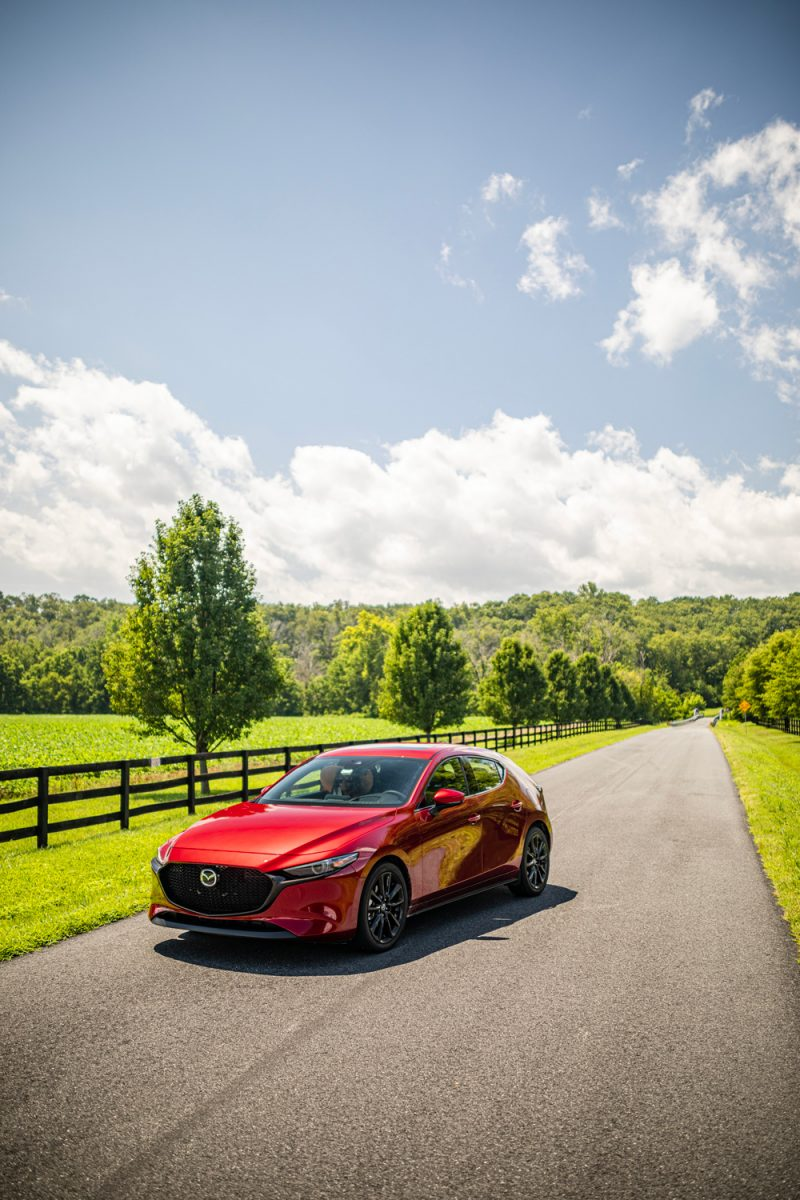 Tips for Traveling During COVID-19 featured by top US travel blogger, Alicia Tenise. | Travel Tips by popular D.C. travel blogger, Alicia Tenise: image of a red Mazda car parked in the middle of a road surrounded by grassy fields and trees.