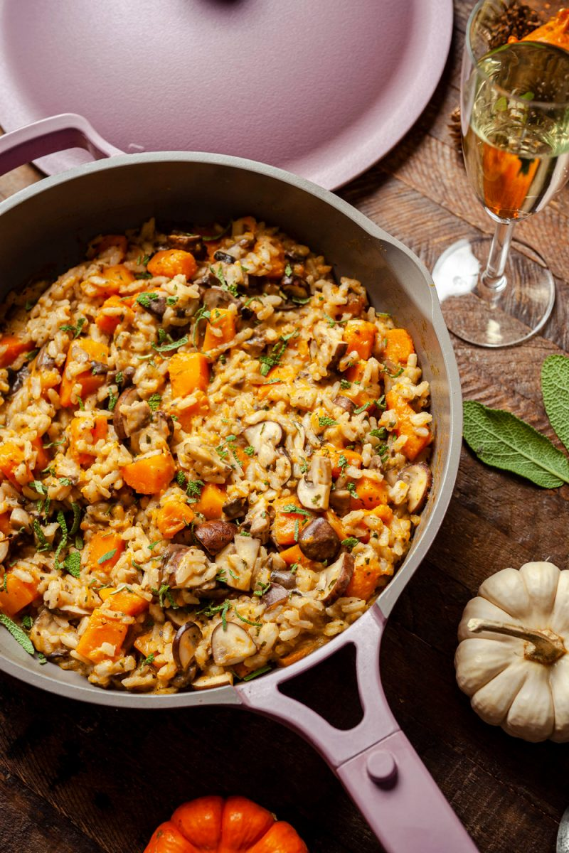 Butternut Squash and Mushroom Risotto Recipe  Trader Joe's Wine by popular D.C. lifestyle blogger, Alicia Tenise: image of a pan of butternut squash and mushroom risotto next to wine glass and some small orange and white pumpkins.