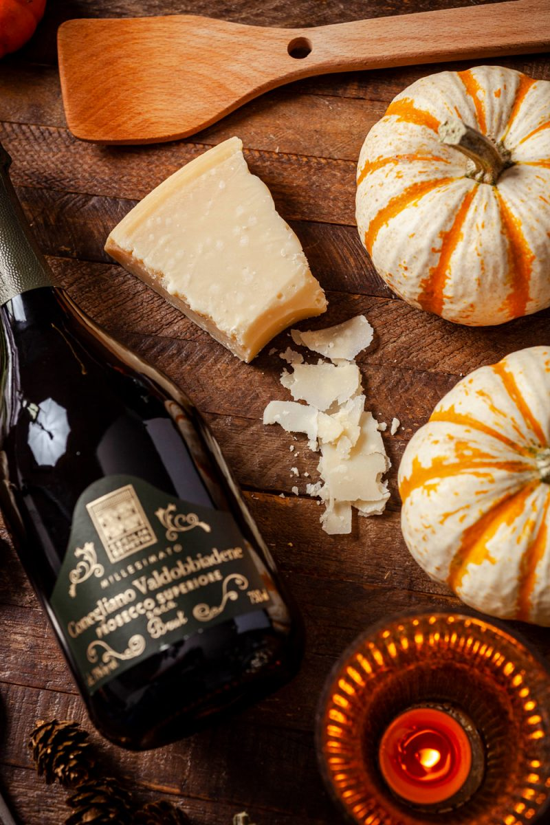 Cecilia Beretta Conegliano Valdobbiadene Prosecco Brut Superiore  Trader Joe's Wine by popular D.C. lifestyle blogger, Alicia Tenise: image of a bottle of Trader Joe's wine laying next to some some pumpkins, and parmesan cheese.