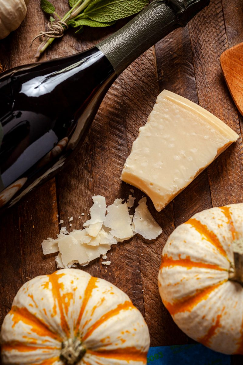 Trader Joe's Grated Parmesan  Trader Joe's Wine by popular D.C. lifestyle blogger, Alicia Tenise: image of a bottle of Trader Joe's wine laying next to some some pumpkins, and parmesan cheese.