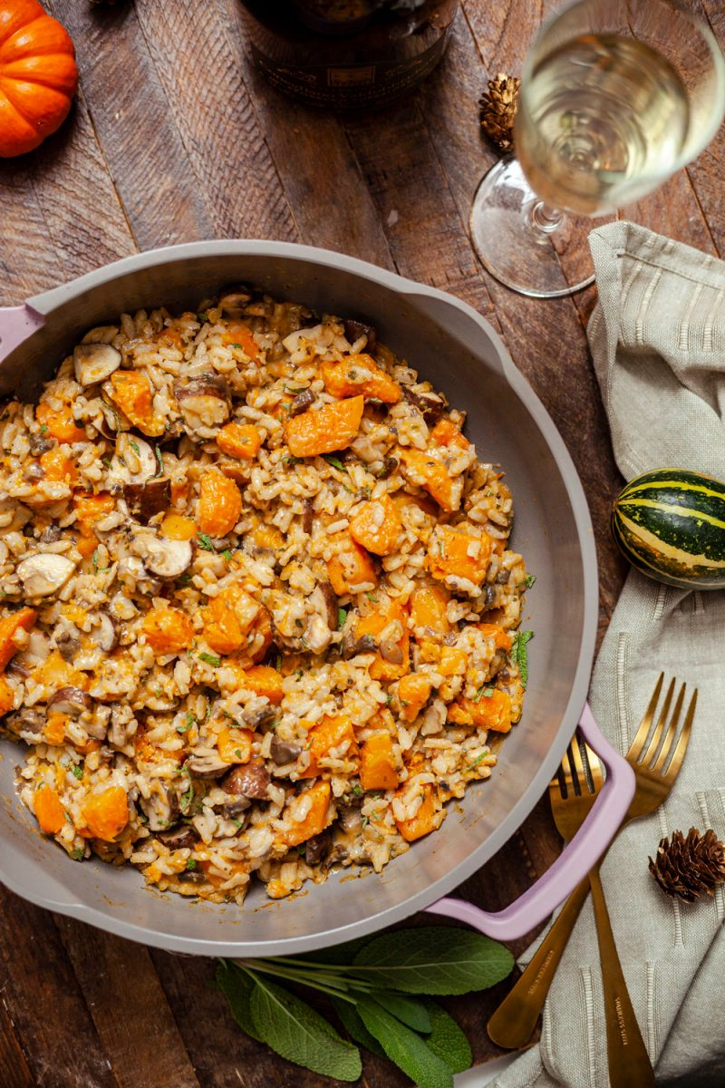 Trader Joe's Fall Recipe and Wine Pairing  Trader Joe's Wine by popular D.C. lifestyle blogger, Alicia Tenise: image of a pan of butternut squash and mushroom risotto next to a wine glass, gold forks, linen napkin, and small orange pumpkin.