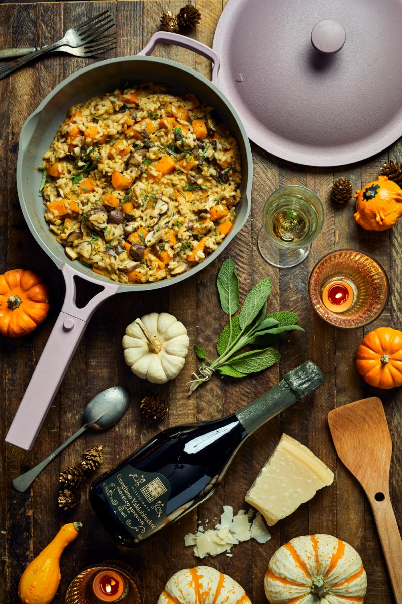 Butternut Squash and Mushroom Risotto   Trader Joe's Wine by popular D.C. lifestyle blogger, Alicia Tenise: image of a bottle of Trader Joe's wine laying next to some some pumpkins, parmesan cheese, silverware, and a pan of butternut squash and mushroom risotto.