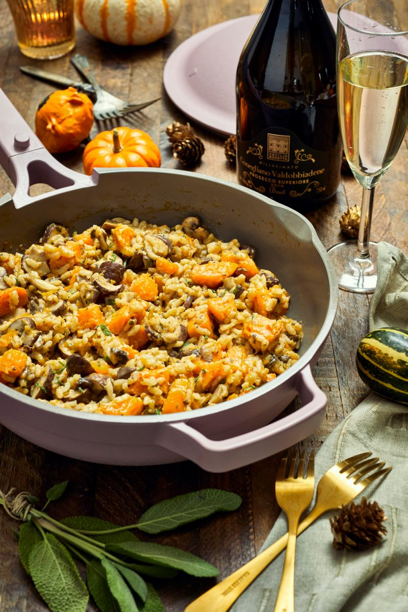 Trader Joe's Fall Recipe  Trader Joe's Wine by popular D.C. lifestyle blogger, Alicia Tenise: image of a bottle of Trader Joe's wine next to some some pumpkins, cheese, silverware, and a pan of butternut squash and mushroom risotto.