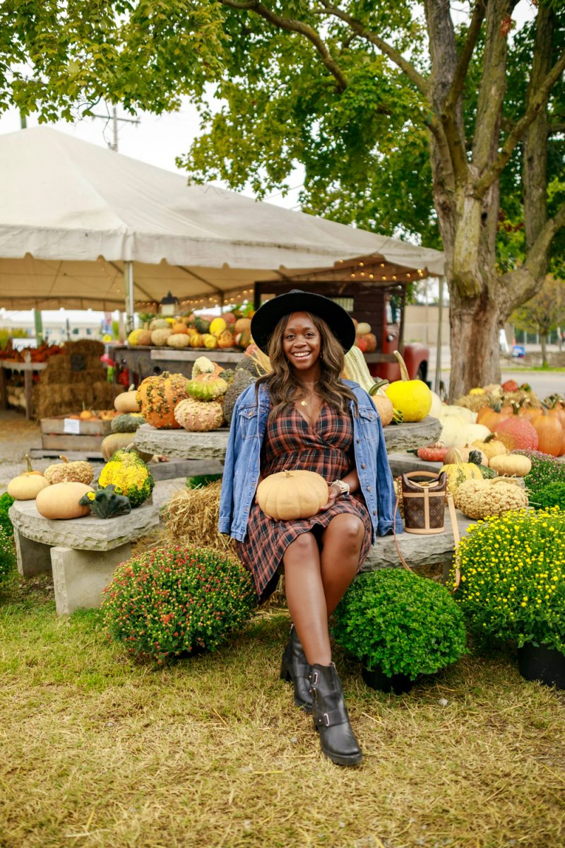 Professional Blogging by popular D.C. lifestyle blogger, Alicia Tenise: image of Alicia Tenise visiting a pumpkin patch and wearing a Madewell Plaid Short Sleeve Tiered Faux Wrap Minidress, black hat, denim jacket and black ankle boots.