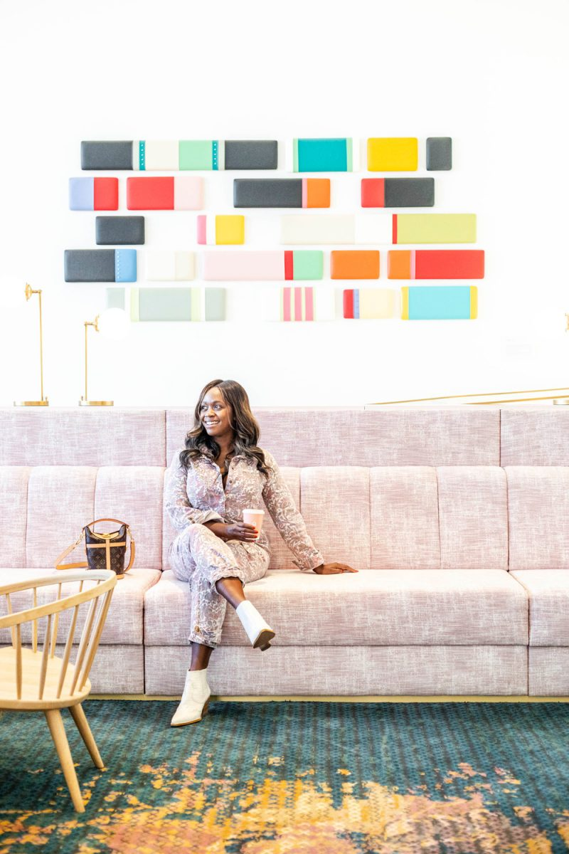 Quirk Hotel Charlottesville |Things to do in Charlottesville by popular D.C. travel blog, Alicia Tenise: image of Alicia Tenise sitting in the Quirk Hotel Lounge.
