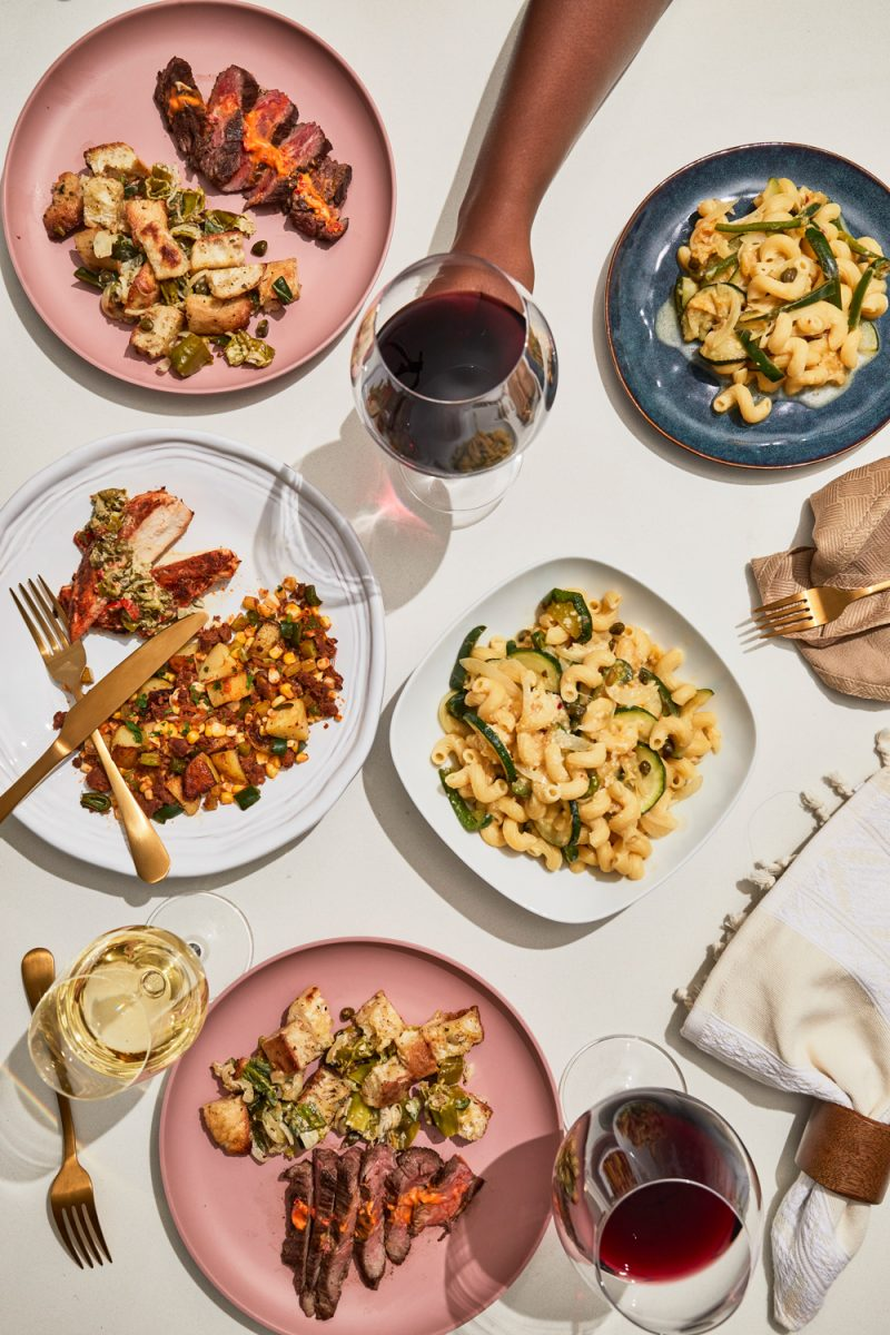 Blue Apron Review by popular D.C. food blogger, Alicia Tenise: image of Alicia Tenise holding a glass of red wine on a table filled with plates of Blue Apron food.