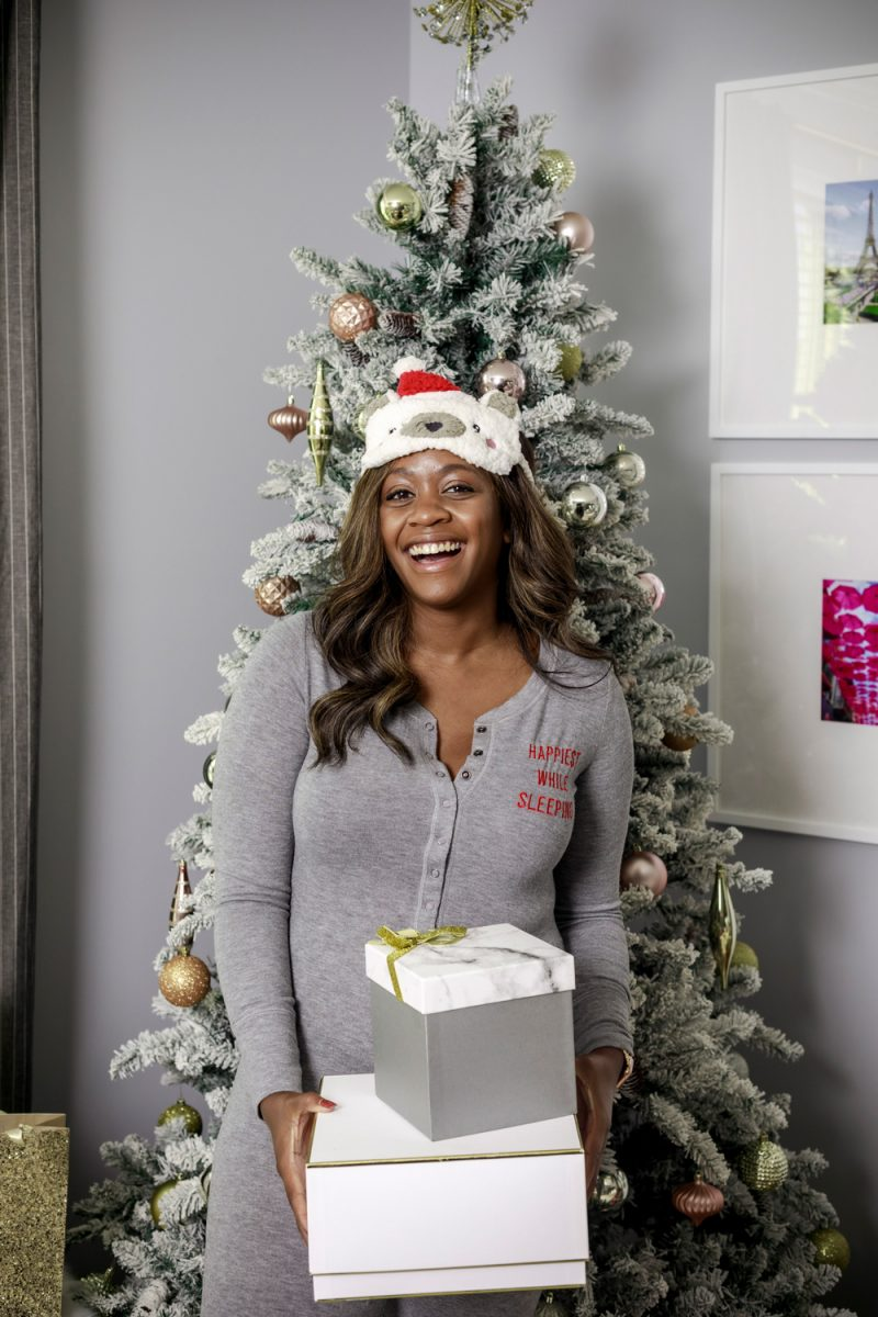 Aerie Softest® Sleep Plush Jumpsuit and Sherpa Sleep Mask | Christmas Morning Pajamas by popular D.C. fashion blogger, Alicia Tenise: image of a Alicia Tenise standing in front of a flocked Christmas tree and holding some wrapped presents while wearing a Aerie Softest® Sleep Plush Jumpsuit and Aerie Sherpa Sleep Mask.