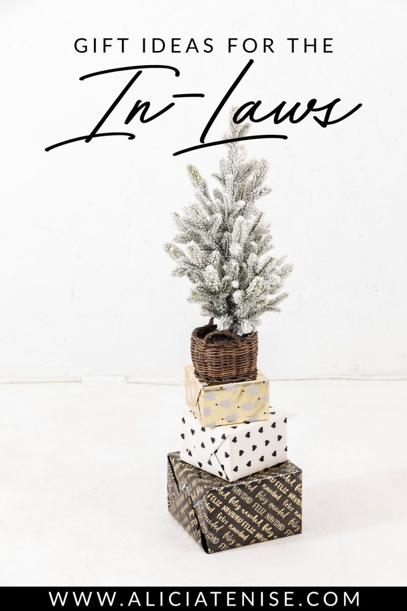 Gift Ideas for the In-Laws | Gifts for Inlaws by popular D.C. life and style blogger, Alicia Tenise: image of a flocked tree in a wicker basket resting on top of three stacked wrapped presents.