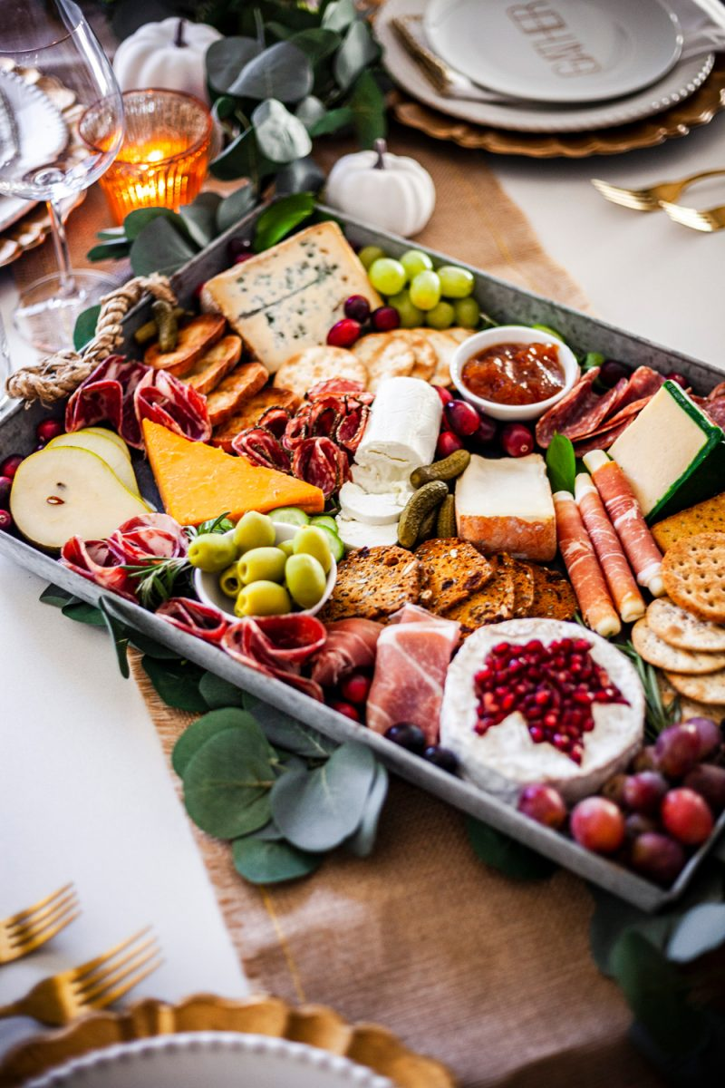 Thanksgiving Cheese and Charcuterie | Thanksgiving Tablescape by popular D.C. life and style blogger, Alicia Tenise: image of a table set with a burlap runner, gold utensils, eucalyptus leaves garland, gold plate chargers, white china, mini white pumpkins, clear wine glasses, gold and white cloth napkins, and a charcuterie board.