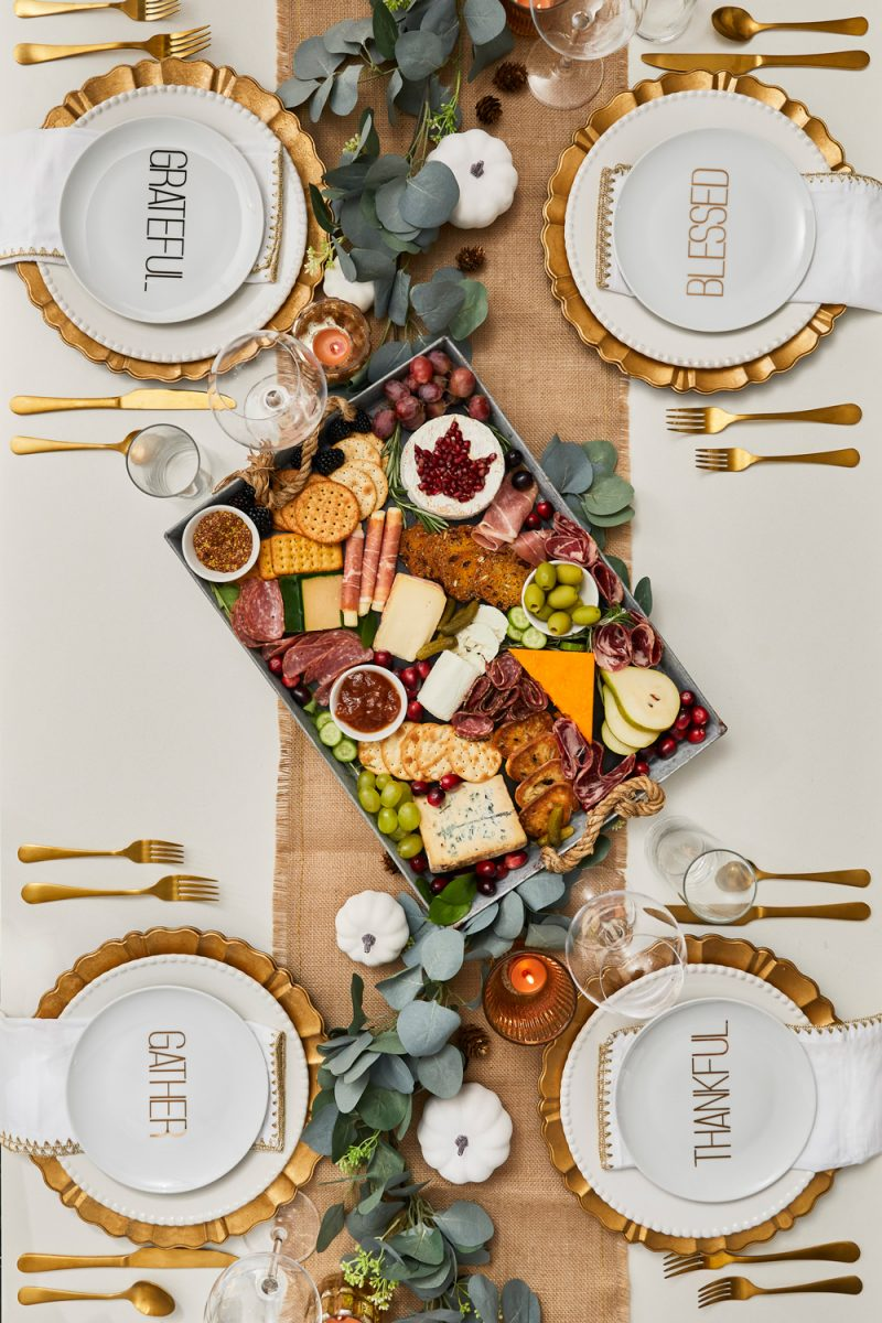 Thanksgiving Tablescape, Thanksgiving Cheese and Charcuterie Board | Thanksgiving Tablescape by popular D.C. life and style blogger, Alicia Tenise: image of a table set with a burlap runner, gold utensils, eucalyptus leaves garland, gold plate chargers, white china, mini white pumpkins, clear wine glasses, gold and white cloth napkins, and a charcuterie board.