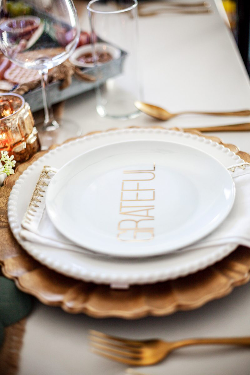 Thanksgiving Tablescape by popular D.C. life and style blogger, Alicia Tenise: image of a table set with a burlap runner, gold utensils, eucalyptus leaves garland, gold plate chargers, white china, mini white pumpkins, clear wine glasses, gold and white cloth napkins, and a charcuterie board.