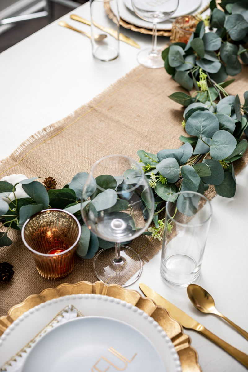 Thanksgiving Tablescape by popular D.C. life and style blogger, Alicia Tenise: image of a table set with a burlap runner, gold utensils, eucalyptus leaves garland, gold plate chargers, white china, mini white pumpkins, clear wine glasses, and a gold and white cloth napkins.