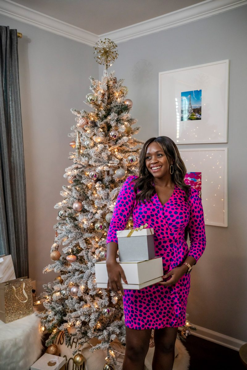 Scoop Women's Ruffle Front Dress with Puff Sleeves |Holiday Outfits by popular D.C. fashion blogger, Alicia Tenise: image of Alicia Tenise wearing a Walmart Scoop Women's Ruffle Front Dress with Puff Sleeves and standing in front of a flocked Christmas tree while holding some presents.
