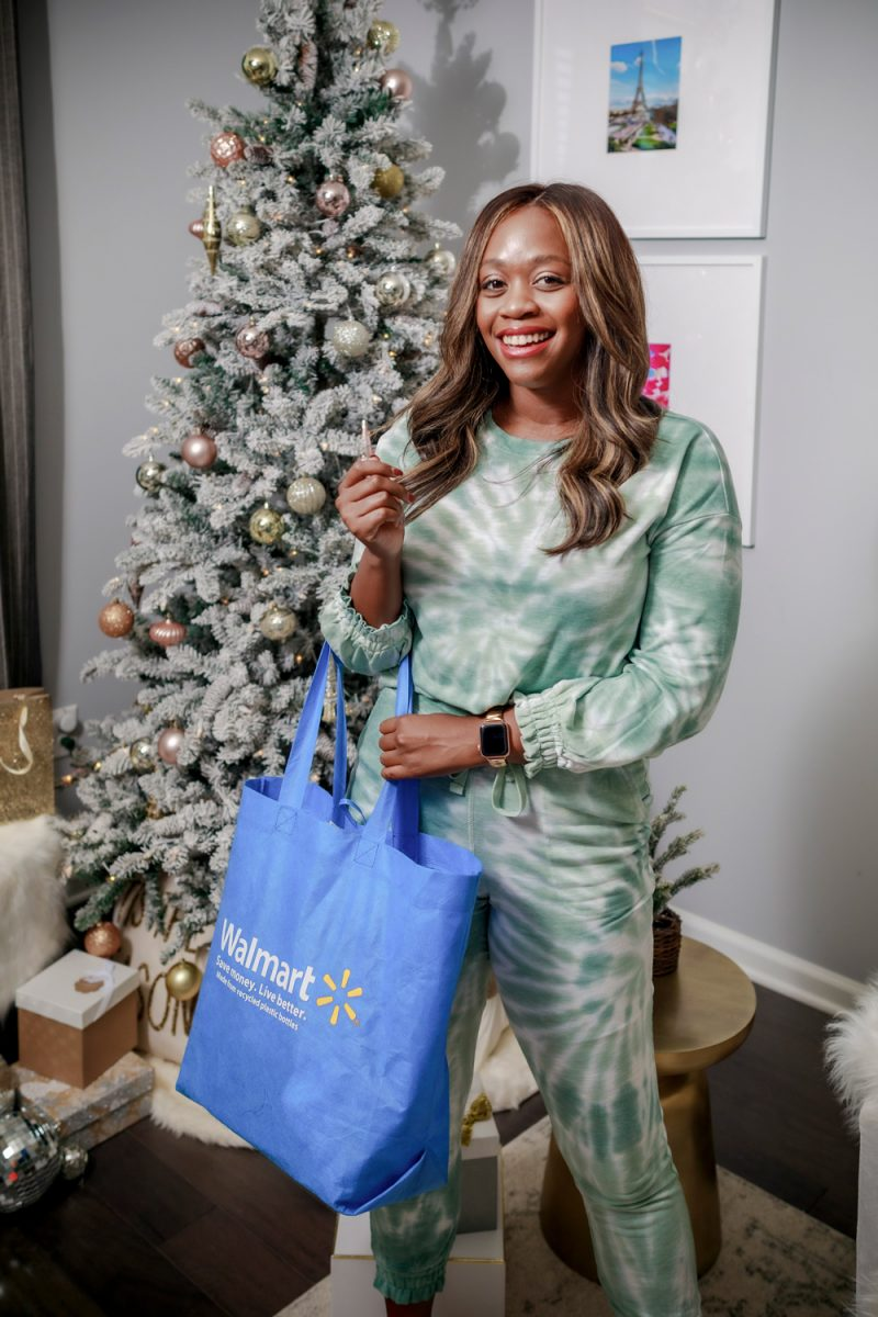 Holiday Shopping by popular D.C. lifestyle blogger, Alicia Tenise: image of Alicia Tenise wearing a Walmart Scoop Women's Tie Dye Sweatshirt with Drawstring Waist and a Walmart Scoop Women's Tie Dye Joggers with Elasticized Cuffs and holding a reusable Walmart shopping bag while standing in front of her flocked Christmas tree.