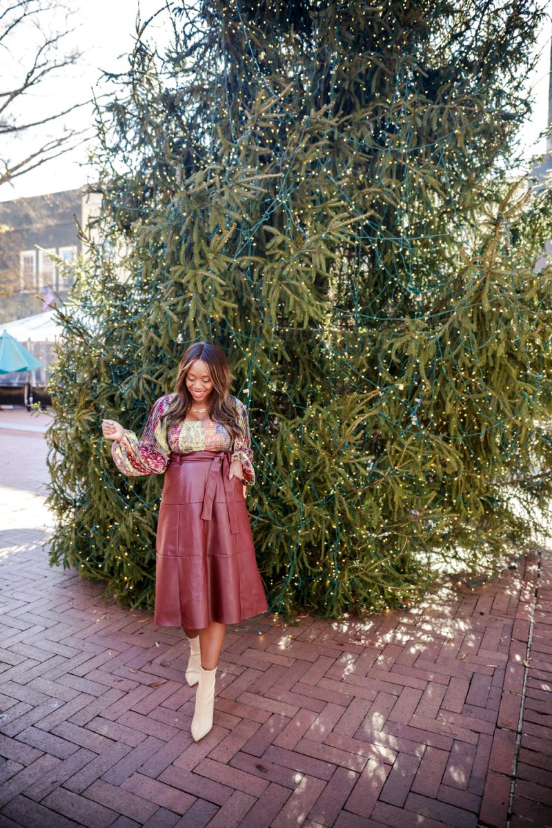 Leather Skirt by popular D.C. fashion blogger, Alicia Tenise: image of a woman standing in front of a Christmas tree and wearing a Anthropologie Tara Smocked Blouse, Anthropologie Coralia Faux Leather Midi Skirt, white ankle boots and carrying a Louis Vuitton DUFFLE BAG.