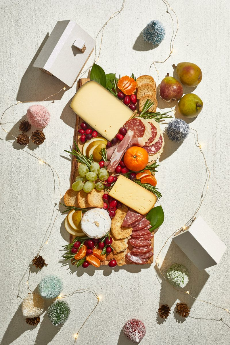 Holiday Cheese and Charcuterie Board |Charcuterie Board by popular D.C. lifestyle blogger, Alicia Tenise: image of a holiday Charcuterie board filled with specialty meats,crackers, cheese, fruit, and fresh rosemary sprigs.