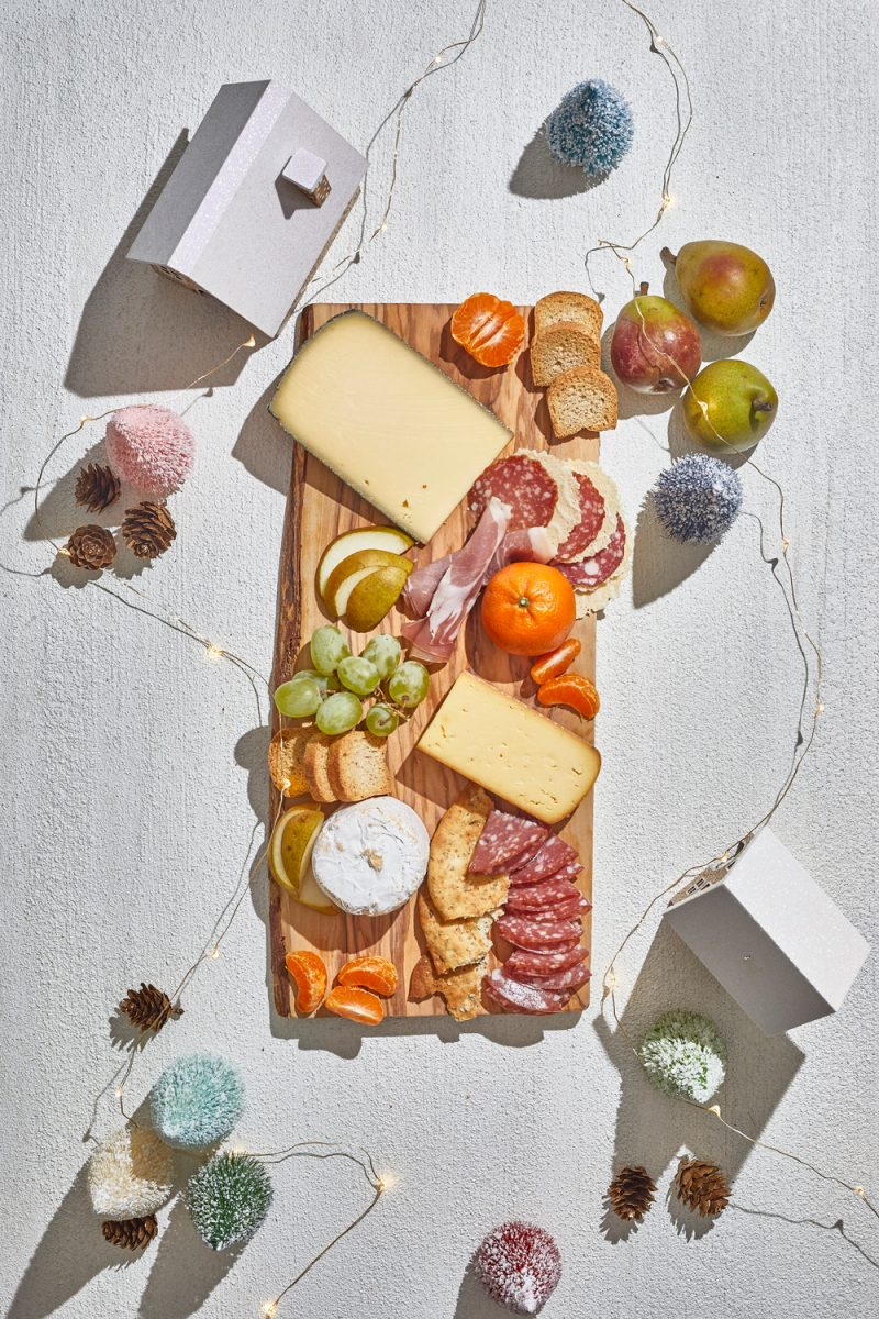 Charcuterie Board by popular D.C. lifestyle blogger, Alicia Tenise: image of a holiday Charcuterie board filled with specialty meats,crackers, cheese, fruit, and fresh rosemary sprigs.