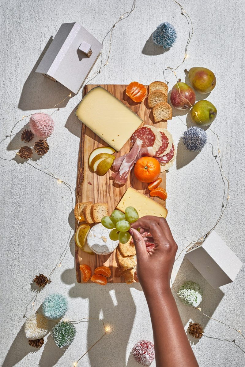 Charcuterie Board by popular D.C. lifestyle blogger, Alicia Tenise: image of Alicia Tenise placing cheese wedges, fruit, and specialty meats down on a wooden board.