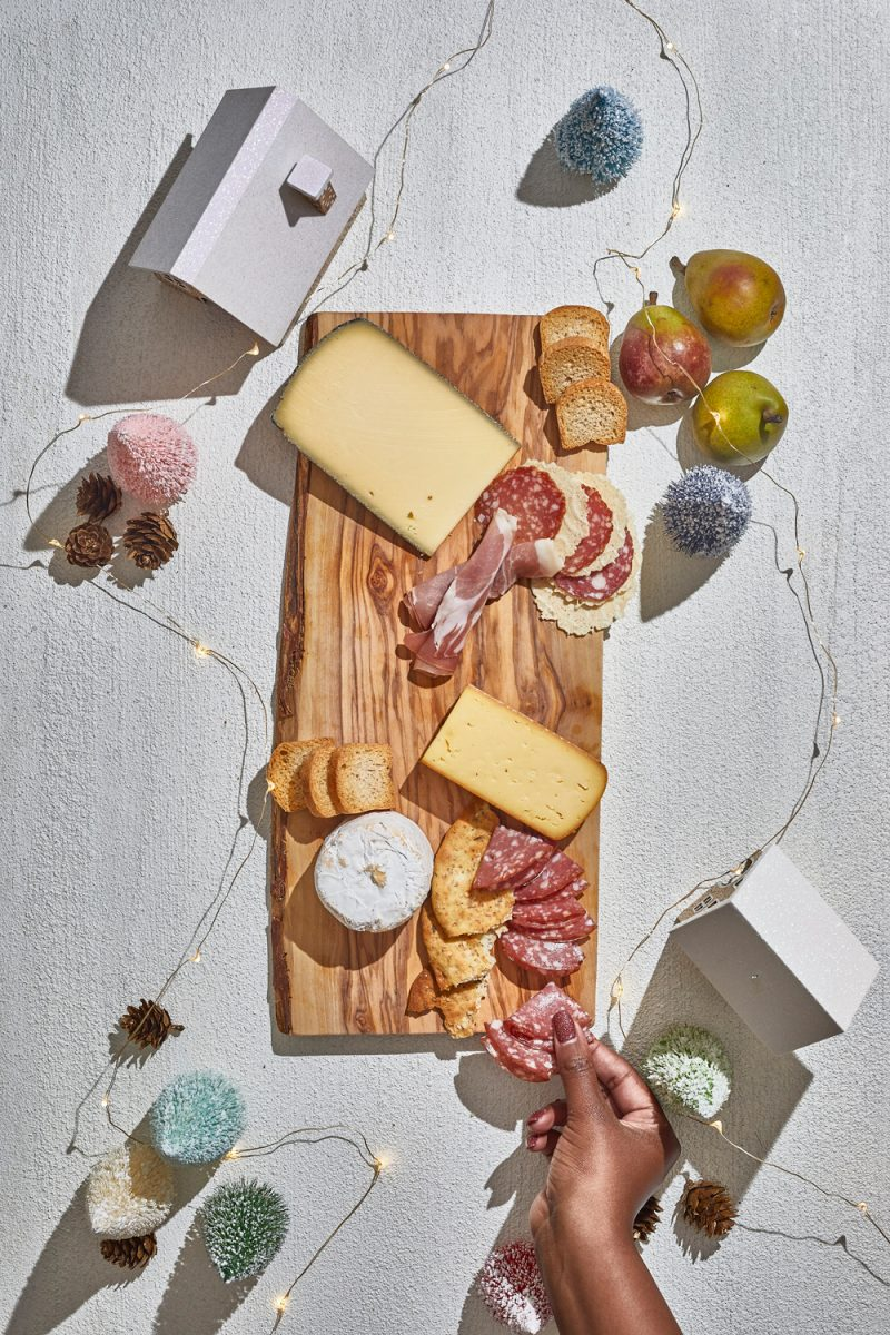 Charcuterie Board by popular D.C. lifestyle blogger, Alicia Tenise: image of Alicia Tenise placing cheese wedges and specialty meats down on a wooden board.