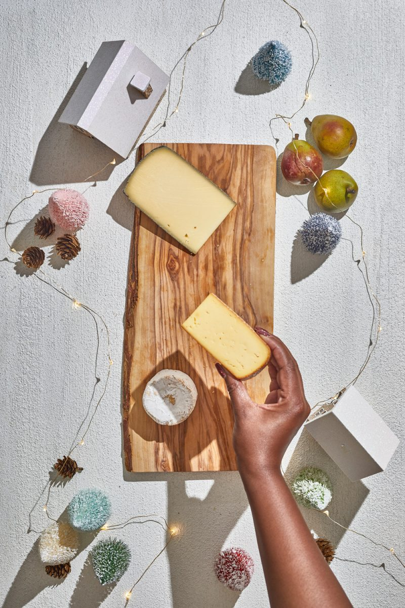 Charcuterie Board by popular D.C. lifestyle blogger, Alicia Tenise: image of Alicia Tenise placing cheese wedges down on a wooden board.