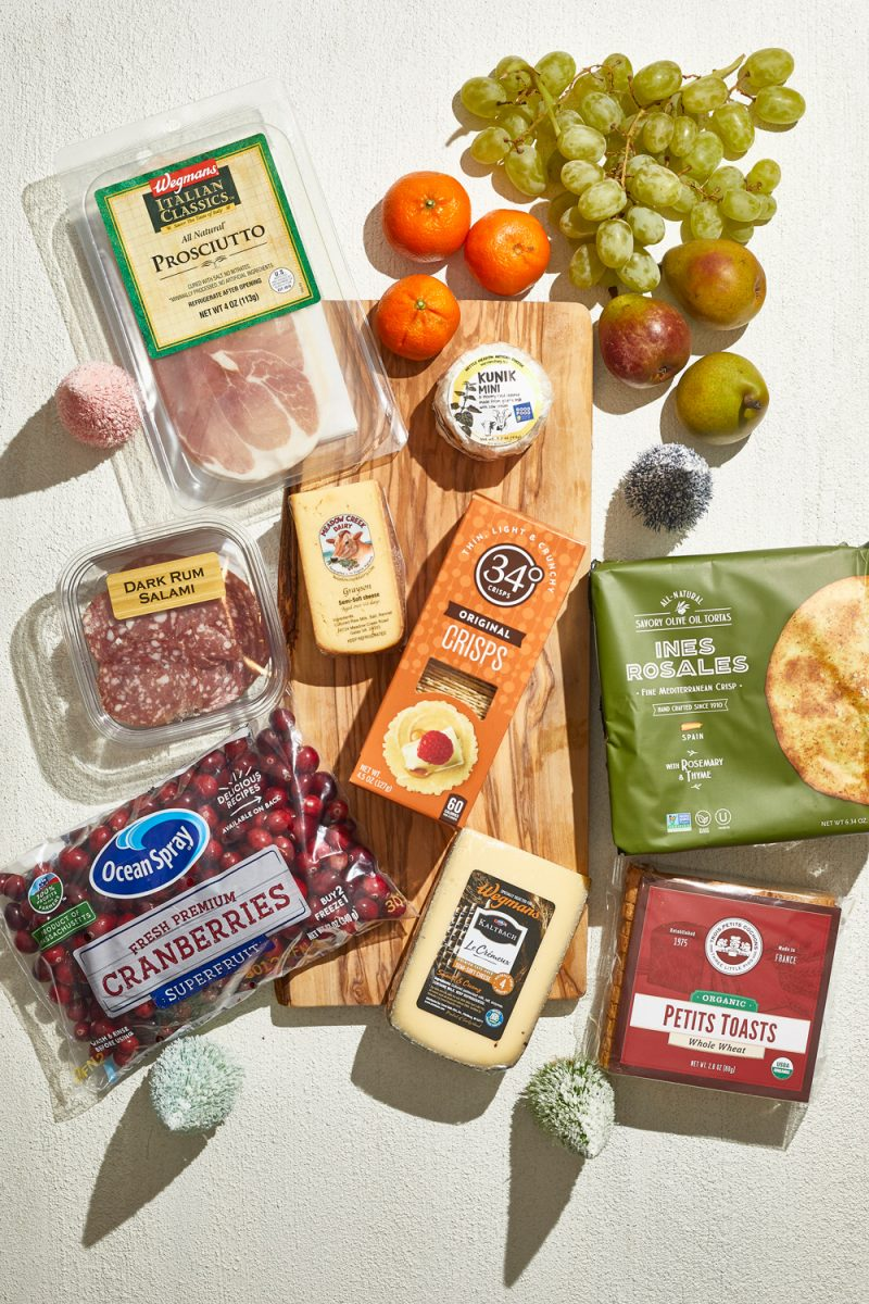Holiday Cheese Board Ingredients |Charcuterie Board by popular D.C. lifestyle blogger, Alicia Tenise: image of specialty cheese, fresh cranberries, specialty meats, crackers, and fruit.