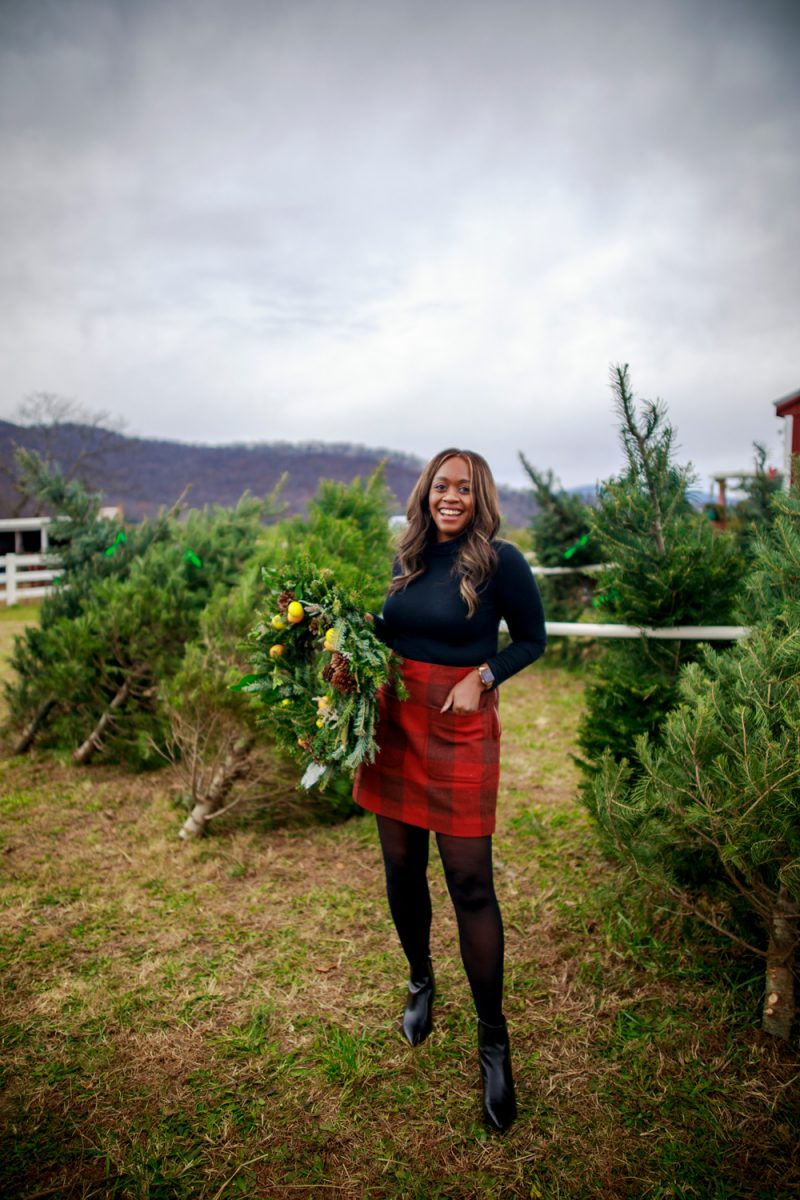 Plaid Skirt from Walmart |Walmart Free Assembly by popular D.C. fashion blogger, Alicia Tenise: image of Alicia Tenise standing outside at a Christmas tree farm and wearing a Free Assembly red plaid skirt, black tights, black turtleneck top, and black ankle boots.