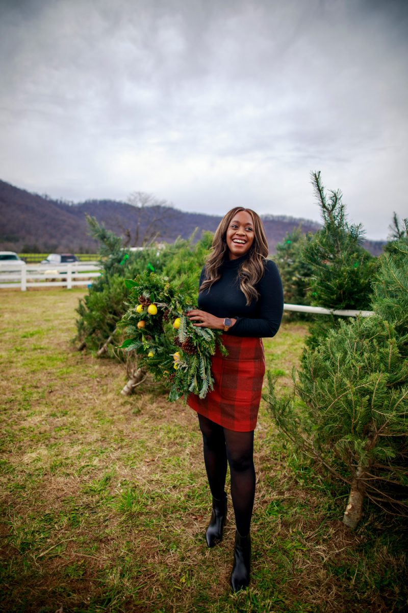 Walmart Free Assembly Women's Stamp Skirt | Walmart Free Assembly by popular D.C. fashion blogger, Alicia Tenise: image of Alicia Tenise standing outside at a Christmas tree farm and wearing a Free Assembly red plaid skirt, black tights, black turtleneck top, and black ankle boots.