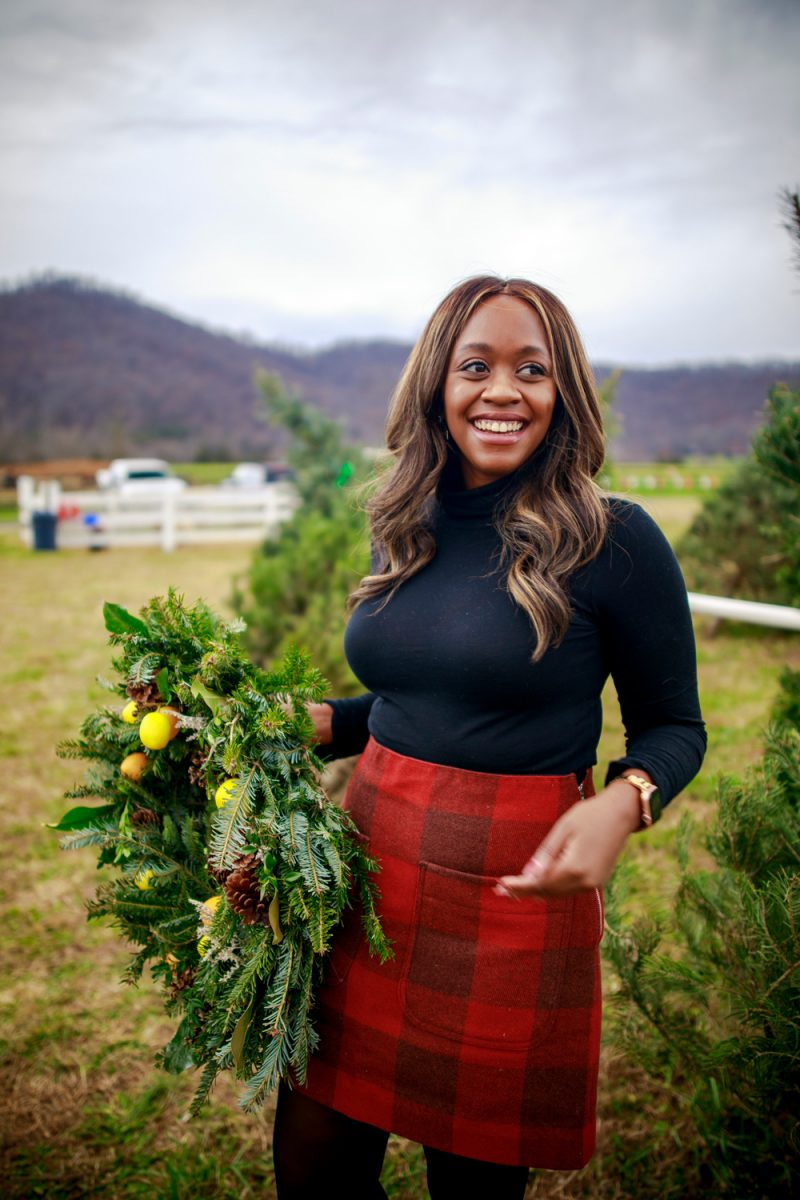 Walmart Free Assembly by popular D.C. fashion blogger, Alicia Tenise: image of Alicia Tenise standing outside at a Christmas tree farm and wearing a Free Assembly red plaid skirt, black tights, black turtleneck top, and black ankle boots.