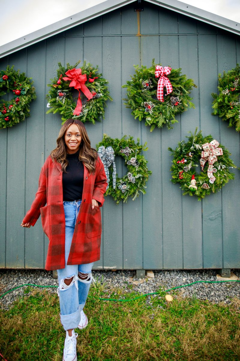 Plaid Coat from Walmart |Walmart Free Assembly by popular D.C. fashion blogger, Alicia Tenise: image of Alicia Tenise standing outside at a Christmas tree farm and wearing a Free Assembly red plaid cocoon coat, distressed denim, and black turtleneck shirt.
