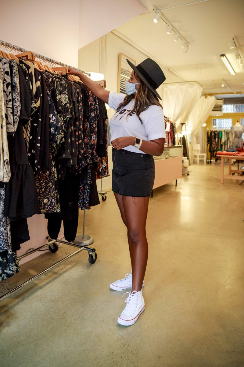Boutique Shopping in Asheville NC | Savings Challenge by popular D.C. lifestyle blogger, Alicia Tenise: image of Alicia Tenise wearing white converse high top sneakers, white t-shirt, black felt hat, and a black denim mini skirt while looking through a rack of black clothing.