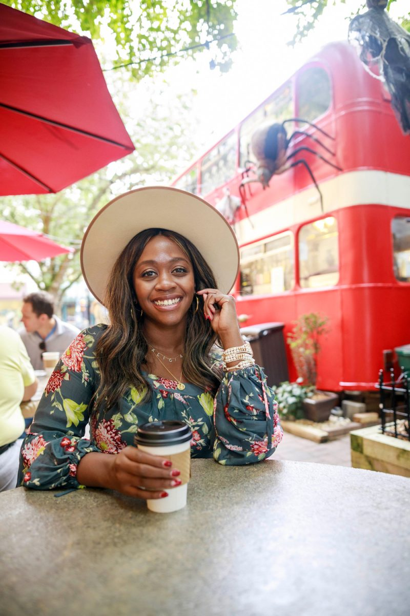 Coffee at Double D's Coffee & Desserts in Asheville NC |Savings Challenge by popular D.C. lifestyle blogger, Alicia Tenise: image of Alicia Tenise sitting at a outdoor table with a cup of coffee next to a black double decker bus.