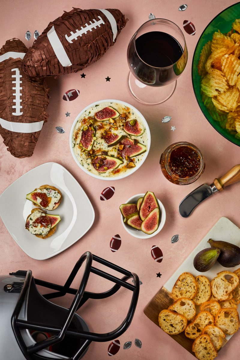 Football Party Ideas by popular D.C. lifestyle blogger, Alicia Tenise: image of chocolate covered strawberries, bowl of potato chips, glass of red wine, sliced figs, crostini bread slices, and bacon wrapped potato bites.