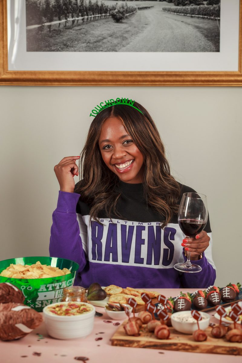TAILGATE WOMEN'S BALTIMORE RAVENS COLORBLOCK SWEATSHIRT |Football Party Ideas by popular D.C. lifestyle blogger, Alicia Tenise: image of Alicia Tenise sitting in front of a table set wiht. chocolate covered strawberries, bowl of potato chips, glass of red wine, sliced figs, crostini bread slices, and bacon wrapped potato bites.