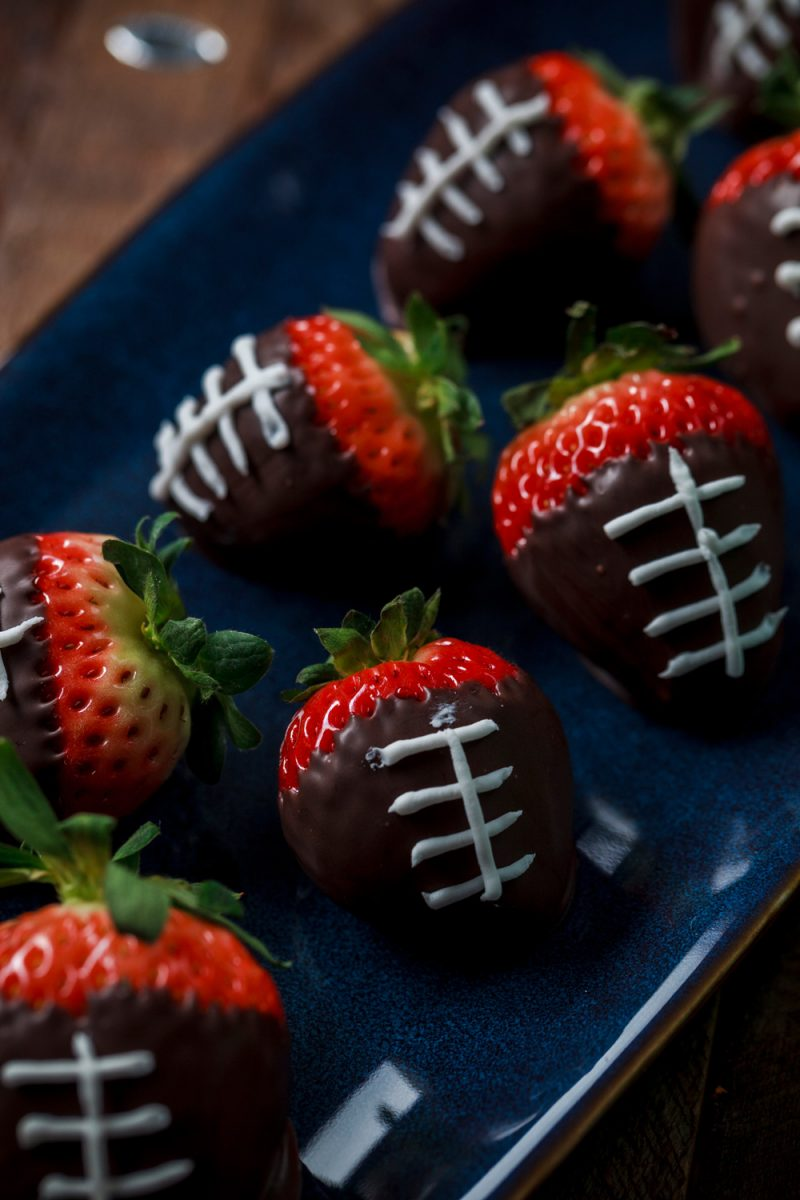 SUPER EASY FOOTBALL PARTY FOOD IDEAS 1/24/17 Tweet Pin 5.8K Share 32 5.8KSHARES Disclosure: This post contains some affiliate links, which means that if you click on one of the product links and make a purchase, I may receive a commission. This does not cost you anything additional, and helps me to keep the rest of my content free, so thank you! APPETIZERS AND SNACKS PERFECT FOR YOUR TAILGATE, HOMEGATE, OR BIG GAME PARTY 4 Super Easy Football Party Food Ideas Pause Unmute Remaining Time -2:55 With the Big Game coming up, I wanted to share some super easy football-themed snack ideas. These are all easy, and can be made at the last minute if you are suddenly inspired to up the game of your game day spread. And these aren't just for a Big Game party… they are all easy enough to create for any game-watching get-together, tailgate, or even a sports-themed birthday party, so you will definitely want to pin these ideas for later! CHECK OUT FOUR SUPER EASY FOOTBALL PARTY FOOD IDEAS IN THIS YOUTUBE VIDEO: Speaking of, check out more football party inspiration on my Football Party board on Pinterest, and stay tuned to the blog later this week for a post on easy football decorations for your big game watch party. The thing that's great about a football party is that it's easy to incorporate creativity and DIY. Pretty much anything brown can become a little football with a little decoration. You'll see a lot of that in this post. football party food ideas - football brownie bites Football brownies. You can make these the easy way with store-bought brownie bites, or if you have a little extra time, you can shape homemade brownies like footballs (see more on that below). Either way, brownies or brownie bites can become little footballs by adding a little white cake decorating icing. Just pipe on some little laces, and this snack is ready to go. easy football party food ideas - football brownies For homemade football brownies shaped like little footballs, make your favorite browni