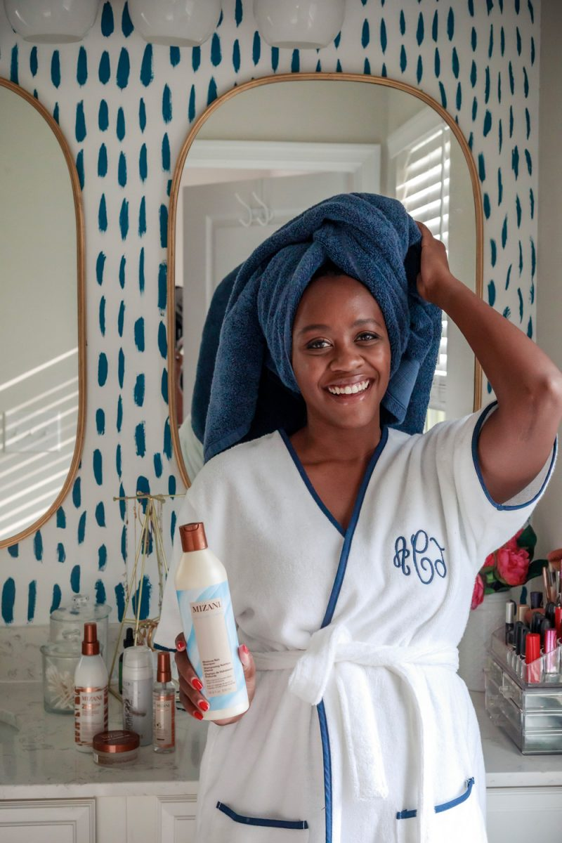 Weezie Short Robe, Mizani Hair Products | Natural Hair Products by D.C. beauty blogger, Alicia Tenise: image of Alicia Tenise, standing in her bathroom and wearing a white monogrammed robe with a blue towel wrapped around her head while holding a bottle of Mizani shampoo.