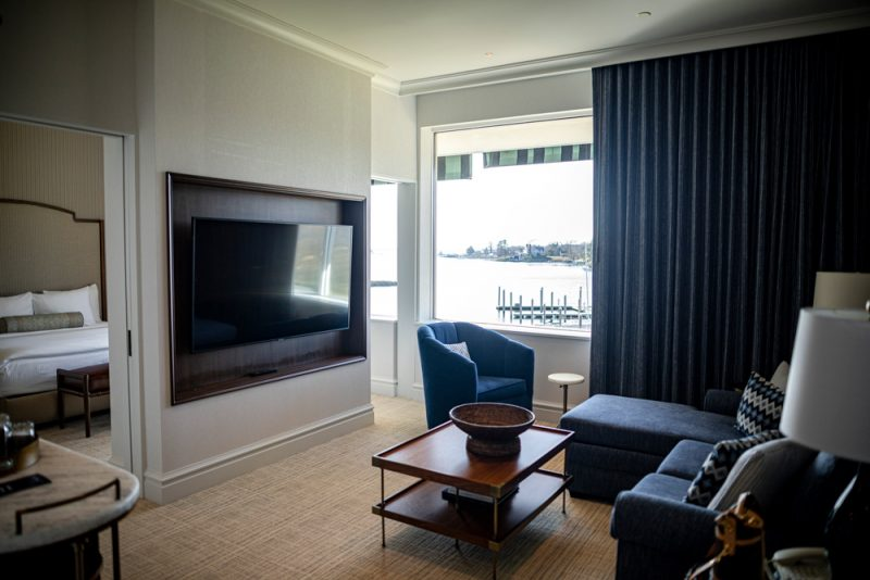 The Tides Inn Ashburn Suite |Tides Inn in Irvington by popular D.C. travel blogger, Alicia Tenise: image of a hotel room decorated with a flat screen t.v., blue sectional couch, blue armchair, and blue fabric drapes.