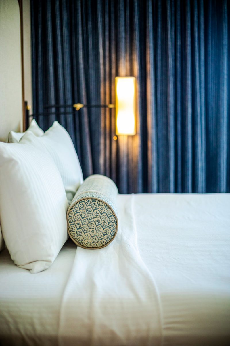The Tides Inn Ashburn Suite |Tides Inn in Irvington by popular D.C. travel blogger, Alicia Tenise: image of a hotel room decorated with blue drapes and a bed with white bedding a blue and white bolster pillow.