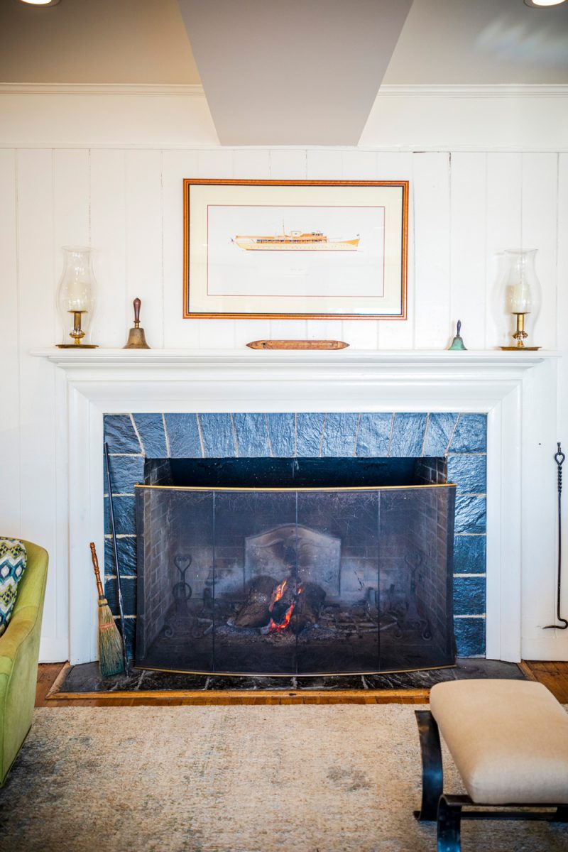 The Tides Inn in Irvington VA |Tides Inn in Irvington by popular D.C. travel blogger, Alicia Tenise: image of a framed print of a ship hanging over a blue tile fireplace with a white mantle.