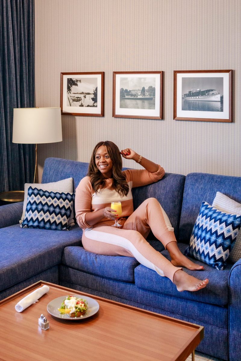 The Tides Inn Ashburn Suite, Clara Colorblocked Jogger Lounge Set |Tides Inn in Irvington by popular D.C. travel blogger, Alicia Tenise: image of Alicia Tenise wearing a color block track suit and sitting on a blue sectional couch.